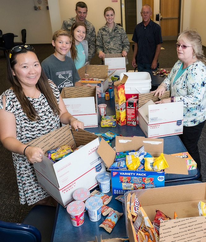 Key spouses and their family members, along with staff from Air Force Research Laboratory's Operations Support Office, assemble care packages for 20 deployed AFRL team members. (U.S. Air Force photo / Alaina Fitzner)