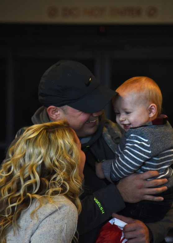 Staff Sgt. Brandon Peterson, 69th Maintenance Squadron aircraft maintenance craftsman, hugs his son Kayden, 1, Dec. 9, 2016, in Grand Forks, N.D. Peterson spent the last six months deployed and wasn't able to see son or wife, Hailey. (U.S. Air Force photo by Senior Airman Ryan Sparks)