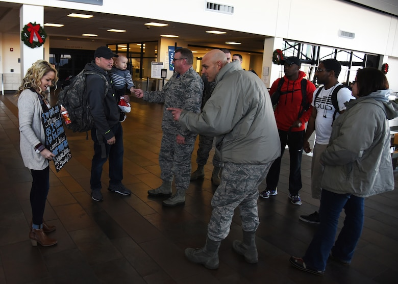 Leadership from the 69th Maintenance Squadron welcome home Airmen from their squadron Dec. 9, 2016, in Grand Forks, N.D. Airmen with the 69th MXS deploy regularly and work to ensure the mission of the 69th Reconnaissance Group is completed at home and abroad. (U.S. Air Force photo by Senior Airman Ryan Sparks)