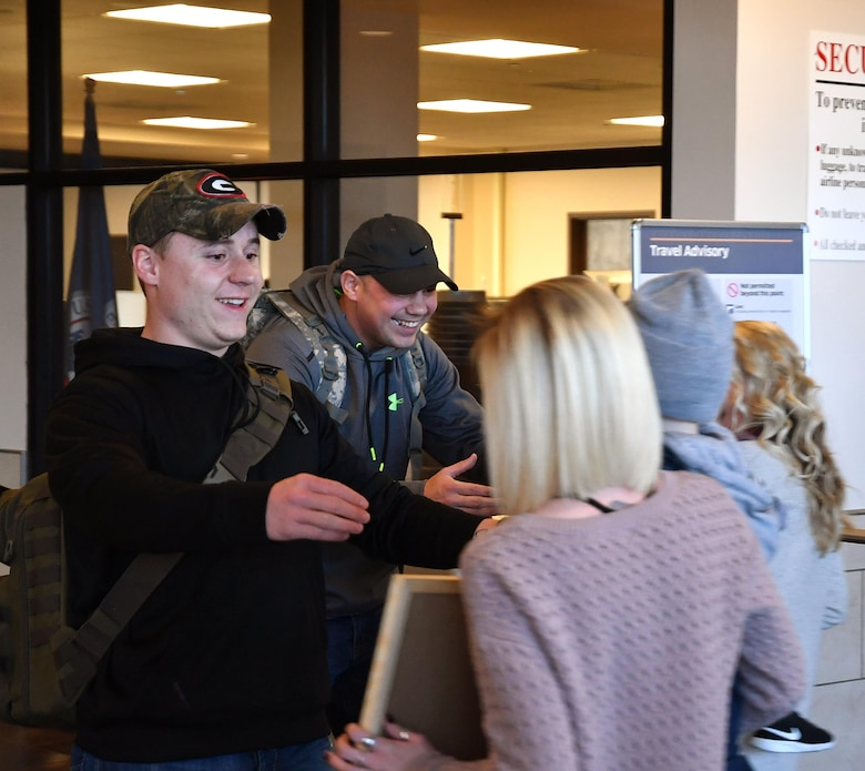 Senior Airman Steven Hayes; 69th Maintenance Squadron aircraft maintenance journeyman; and Staff Sgt. Brandon Peterson; 69th MXS aircraft maintenance craftsman; return from deployment and are welcomed home by their families on Grand Forks International Airport; N.D.; Dec. 9; 2016. Many deployed Airmen will be returning home just in time for the holiday season. (U.S. Air Force photo by Airman 1st Class Elijaih Tiggs)