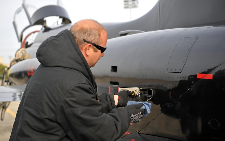 Matt Miller, 9th Maintenance Group T-38 aircraft mechanic, checks the oil in a T-38 Talon engine during a post-flight inspection Dec. 5, 2016, at Beale Air Force Base, California. The mechanics take an oil sample from T-38 engines every 20 flight hours. (U.S. Air Force Photo/Airman Tristan D. Viglianco)