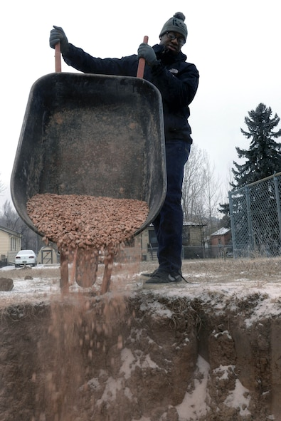 Senior Airman Shaquille Robinson, an intel analyst assigned to the 89th Attack Squadron, pours gravel next to a housing foundation to support its piping in Rapid City, S.D., Dec. 10, 2016. Piping installed in uncompacted ground can develop negative pitch causing stress on the pipe, laying the pipe on a gravel bed will resolve the issue. (U.S. Air Force photo by Airman 1st Class Donald C. Knechtel)