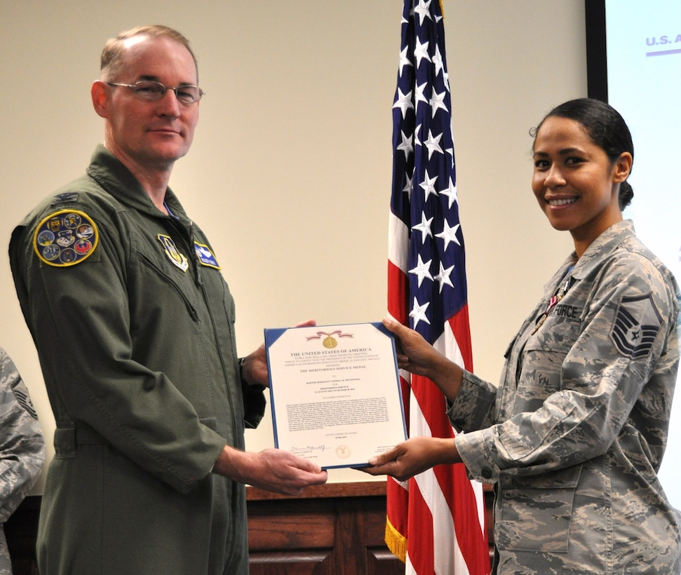 Col. Roger Suro, 340th FTG commander presents a Meritorious Service Medal to Master Sgt. Tainell Pettengill during  the Group's MUTA held Dec. 1-2 at Joint Base San Antonio-Randolph, Texas (Photo by Janis El Shabazz).