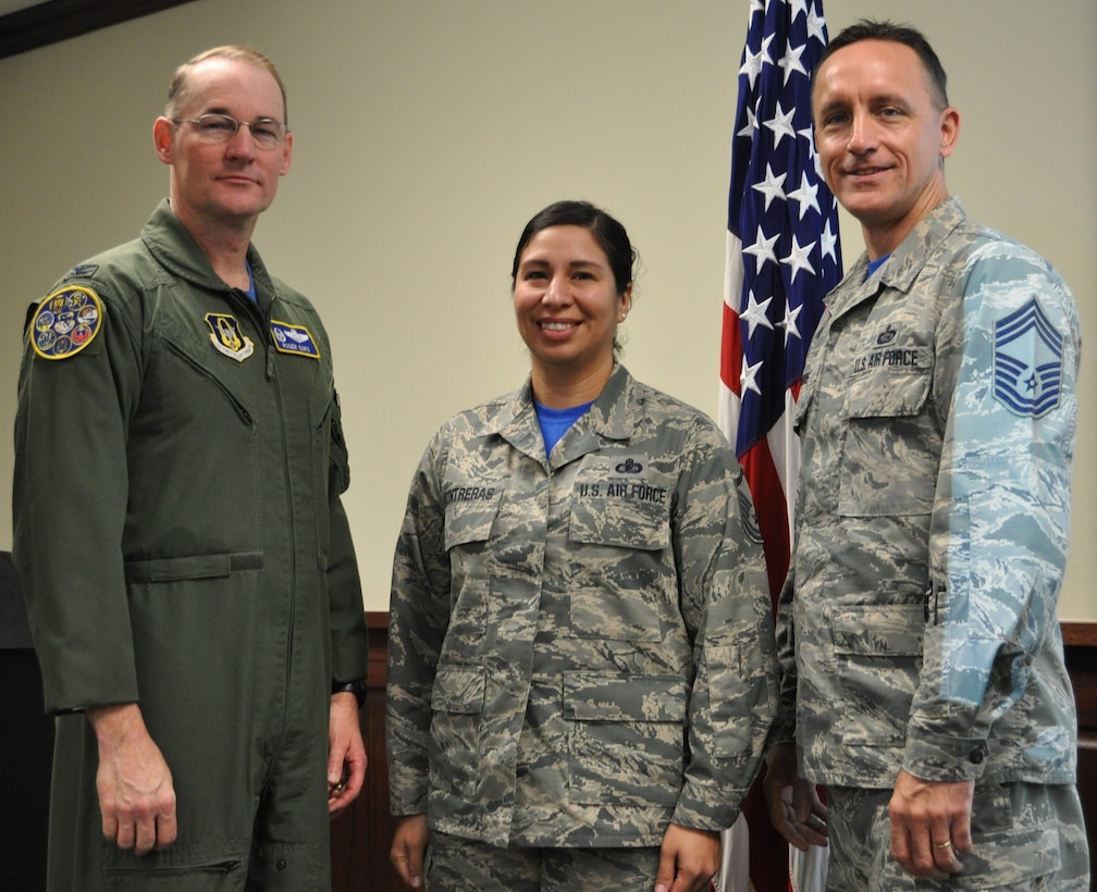 Master Sgt. Vianca Contreras stands with Col. Roger Suro, 340th FTG commander and group superintendent, Chief Master Sgt. Jimmie Morris to receive  a diamond sharp award for the 2nd quarter during the group's Dec. 1 MUTA at Joint Base San Antonio-Randolph, Texas (Photo by Janis El Shabazz).