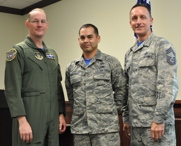 Master Sgt. Gilberto Hernandez stands with Col. Roger Suro, 340th FTG commander and group superintendent, Chief Master Sgt. Jimmie Morris during the group's Dec. 1 MUTA at Joint Base San Antonio-Randolph, Texas  to recognize his selection as a 2016 AFRC Lance P. Sijan nominee (Photo by Janis El Shabazz).