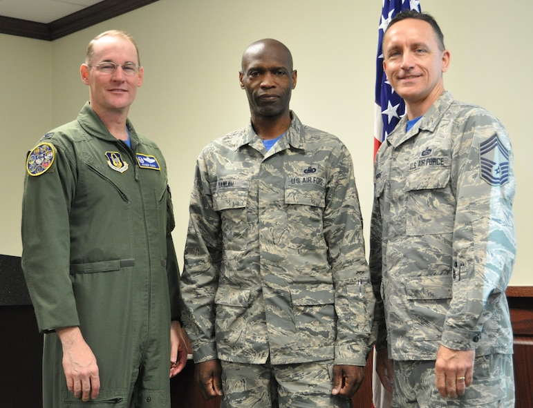 Senior Master Sgt. Kwame Tawiah stands with Col. Roger Suro, 340th FTG commander and group superintendent, Chief Master Sgt. Jimmie Morris during the group's Dec. 1 MUTA at Joint Base San Antonio-Randolph, Texas  to recognize his selection as Humane Society Volunteer of the Month. (Photo by Janis El Shabazz).