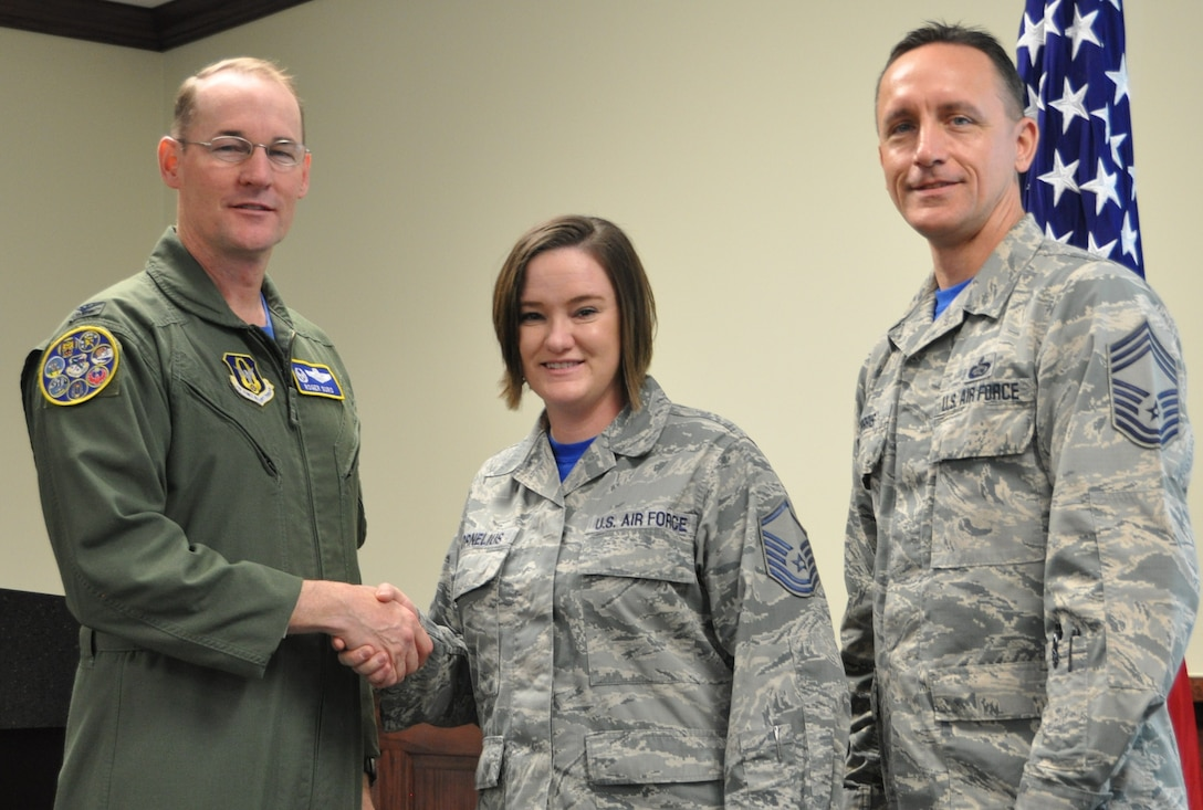 Master Sgt. Sarah Cornelius being coined by Col. Roger Suro, 340th FTG commander for her work with the Green Dot Program, as group superintendent, Chief Master Sgt. Jimmie Morris stands by to congratulate the member during the group's Dec. 1 MUTA at Joint Base San Antonio-Randolph, Texas (Photo by Janis El Shabazz).
