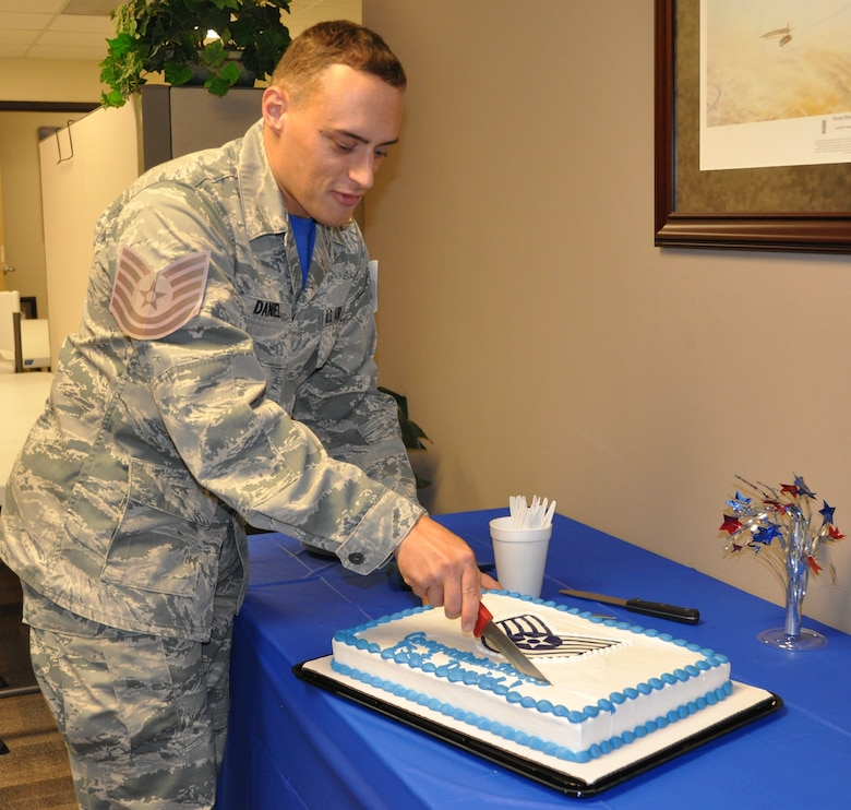 New Tech. Sgt. Brett Daniel serves up pieces of  cake at the celebration honoring his promotion during the Group's MUTA held Dec. 1-2 at Joint Base San Antonio-Randolph, Texas (Photo by Janis El Shabazz).