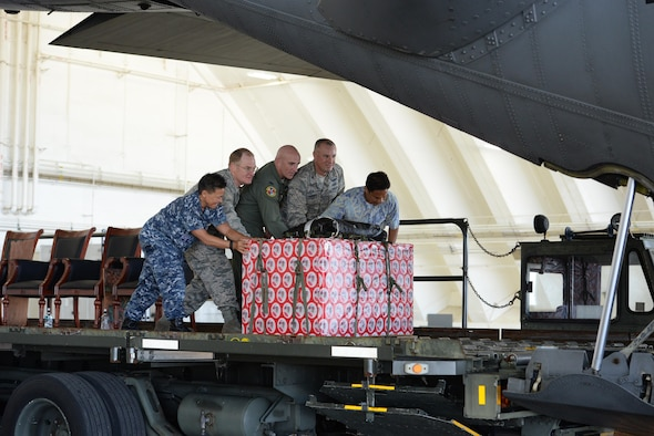 Leaders move a box of donated goods into the back of a C-130 Hercules during the 65th Operation Christmas Drop push ceremony at Andersen Air Force Base, Guam, Dec. 6, 2016. Left to right: Rear Admiral Bette Bolivar, commander, Joint Region Marianas, Brig. Gen. Douglas Cox, 367th Wing commander, Andersen AFB, Guam, Col. Kenneth Moss, 374th Airlift Wing commander, Yokota Air Base, Japan, Col. Scott Zippwald, 515th Air Mobility Operations Wing commander, Joint Base Pearl Harbor Hickam, Hawaii and Manny Hechanova, Associate Director of Telecommunications and Distance Education Operation at the University of Guam. Operation Christmas Drop is the longest running humanitarian airlift operation in the history of the Department of Defense, impacting the lives of more than 20,000 islanders. The people of the Micronesian islands can expect to see service members aboard a C-130 Hercules drop a box, attached to a parachute, filled with rice, fish hooks, educational materials, clothing and toys. (U.S. Air Force photo by Master Sgt. Theanne Herrmann)