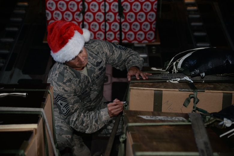 U.S. Air Force Chief Master Sgt. Todd Donaldson, 515th Air Mobility Operations Wing Command Chief, based out of Joint Base Pearl Harbor-Hickam, Hawaii, signs a box of donated goods en route to one of the 54 Micronesian islands as a part of the 65th Operation Christmas Drop Dec. 6, 2016. Operation Christmas Drop is the longest running humanitarian airlift operation in the history of the Department of Defense, impacting the lives of more than 20,000 islanders. The people of the Micronesian islands can expect to see service members aboard a C-130 Hercules drop a box, attached to a parachute, filled with rice, fish hooks, educational materials, clothing and toys. (U.S. Air Force photo by Master Sgt. Theanne Herrmann)