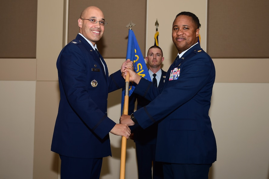 Maj. Douglass Eagleton, 460th outgoing Comptroller Squadron commander, relinquishes the CPTS guidon to Col. David Miller Jr., 460th Space Wing commander, Dec. 12, 2016, during the change of command ceremony on Buckley Air Force Base, Colo. A change of command ceremony represents the formal transfer of responsibility from an outgoing commander to their successor. (U.S. Air Force photo by Airman Jacob Deatherage/Released)
