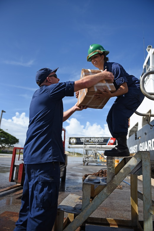 U.S. Coast Guard Senior Chief Petty Officer Mark Petty and Petty Officer 3rd Class Hannah Blanco boatswains's mates aboard the U.S. Coast Guard Cutter Sequoia, load packages onto the ship for Operation Christmas Drop Nov. 22, 2016, at Apra Harbor, Naval Base Guam. The crew of the Sequoia participated in Operation Christmas Drop 2016 by delivering tools, toys, food and water to islands throughout the Pacific. (U.S. Air Force photo by Airman 1st Class Jacob Skovo)