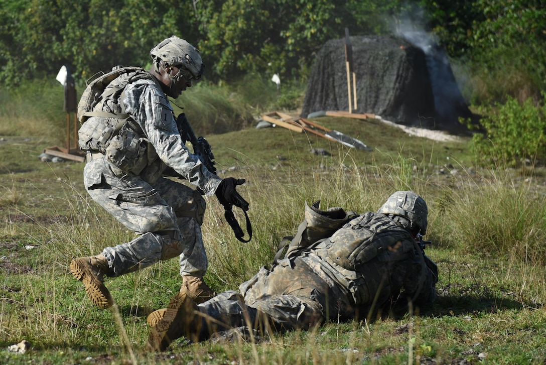 U.S. Army Sgt. Andre Ried, left, and U.S. Army Pfc. Steven Duron, both from the 1st Squad, 1st Platoon, Alpha Company, 4th Battalion, 23rd Infantry Regiment, 2nd Stryker Brigade Combat Team, 2nd Infantry Division, flank a bunker during a squad live-fire exercise Nov. 18, 2016, at Andersen Air Force Base, Guam. The small team flanked a bunker, from a blind spot, as the rest of the squad suppressed simulated targets. Soldiers are assessed quarterly on their ability to navigate, communicate, and apply tactical and infantrymen skills. (U.S. Air Force photo by Airman 1st Class Jacob Skovo)