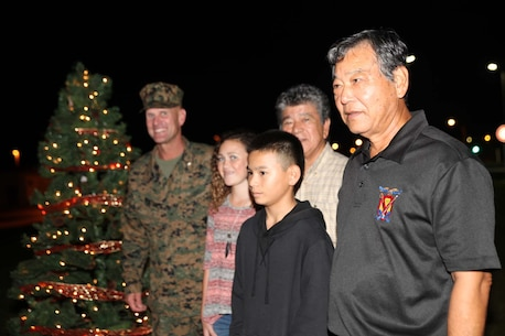 The Second Annual Christmas Tree Lighting was held on Camp Schwab, Okinawa, Japan, Dec. 1, 2016 while III Marine Expeditionary Force Band members play Christmas music. The children from surrounding communities were invited to the ceremony join by Camp Schwab commanding officer, Col. Kevin A. Norton (left), Henoko District Mayor Kayo (middle), and Toyohara District Mayor Miyagi (right).
