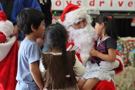 Master Sgt. Anthony Camina, aka Santa Claus, talks to a child from Kin Town during the 2nd annual 3rd Intelligence Battalion Toy Drive Dec. 10, 2016 at the Kin Town Social Welfare Center, Kin Town, Okinawa, Japan. The event hosted the Single Parent Association of Kin, at which children received a party, gifts and candy from Marines with the goal of fostering community relations during the holiday season. Camina, a San Antonio, Texas, native is the community relations coordinator for 3rd Intelligence Battalion.