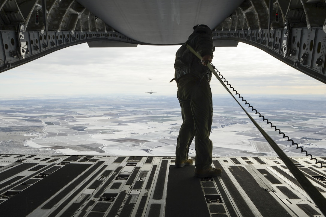 Staff Sgt. Brock Wranik, 62nd Operations Support Squadron loadmaster, looks on as a formation of six C-17 Globmaster IIIs prepare an airdrop over Rainier Drop Zone near Moses Lake, Wash., during the Rainier War exercise Dec. 7, 2016. The airdrop fulfilled one of the objectives of the exercise, which was to resupply members of the Army's 7th Infantry Division with equipment and supplies. (U.S. Air Force photo/Tech. Sgt. Sean Tobin)