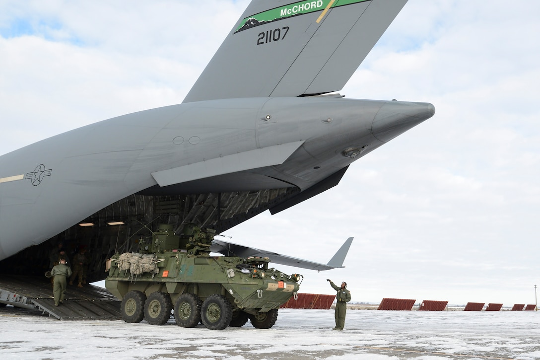 Staff Sgt. Seth Lewis, 7th Airlift Squadron loadmaster, unloads a 7th Infantry Division Stryker onto the snowy ramp at Moses Lake, Wash., during the Rainier War exercise Dec. 7, 2016. In the exercise scenario, Moses Lake was a U.S.-held airfield in hostile territory which required a resupply of equipment and supplies. (U.S. Air Force photo/Tech. Sgt. Sean Tobin)