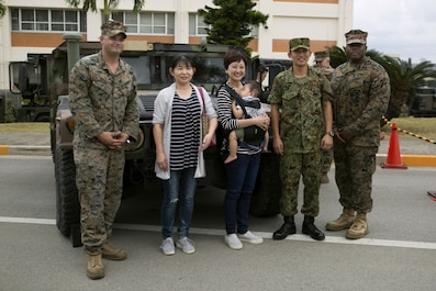 A family poses with Marines and a Japan Ground Self Defense Force service member next to a Humvee Nov. 20, 2016 during the JGSDF Festival on Camp Naha, Okinawa, Japan. The festival celebrated the 6th anniversary of the 15th brigade and the 44th anniversary of Camp Naha. Marines with Combat Assault Battalion, 3rd Marine Division, III Marine Expeditionary Force brought the Humvee, a Light Armored Vehicle and an Assault Amphibious Vehicle for display. Attendees of the festival were able to take photos with the Marines and their vehicles. (U.S. Marine Corps photo by Cpl. Jessica Collins)