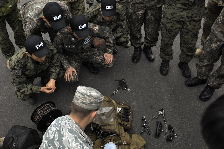 U.S. Air Force Staff Sgt. William Riddle, 8th Civil Engineer Squadron explosive ordinance disposal technician, displays U.S. EOD equipment to Republic of Korea Air Force EOD at Kunsan Air Base, Republic of Korea, Nov. 7, 2016. ROKAF EOD members visited with the U.S. EOD team to learn how they train and what tools and techniques they use. (U.S. Air Force photo by Senior Airman Colville McFee/Released)