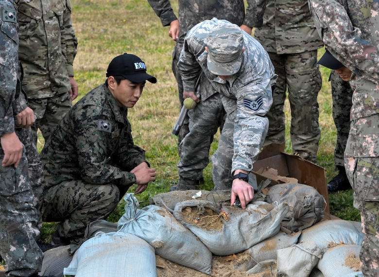 U.S. Air Force Staff Sgt. William Riddle, 8th Civil Engineer Squadron explosive ordnance disposal technician, shows the results of an explosion and how it affects an area to Republic of Korea Air Force EOD members at Kunsan Air Base, Republic of Korea, Nov. 7, 2016. ROK and U.S. Airmen work together to integrate operations more effectively in order to deter aggression in the region. (U.S. Air Force photo by Senior Airman Colville McFee/Released)
