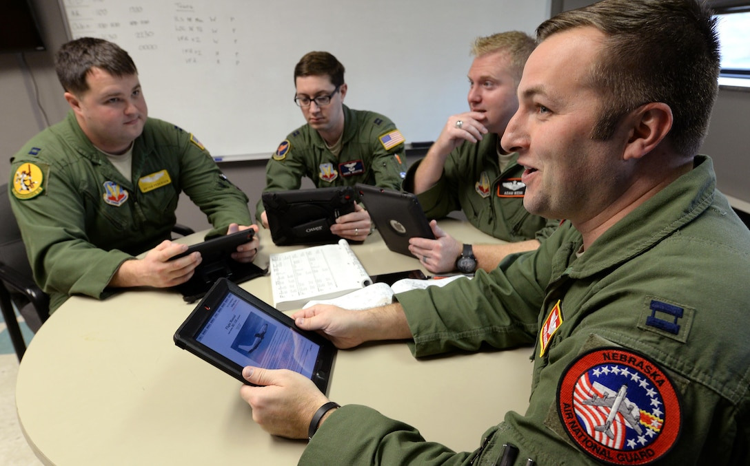 Capt. Bryan Allebone (right), an instructor navigator and fulltime Air National Guard member assigned to the 238th Combat Training Squadron, does mission planning with other Offutt aircrew members Dec. 12, 2016 at Offutt Air Force Base, Neb. The crew members are using electronic flight bags on Apple iPads that have replaced much of the legacy paper processes. Allebone coordinated efforts to get an EFB program approved and stood up at Offutt. (U.S. Air Force photo by Delanie Stafford)