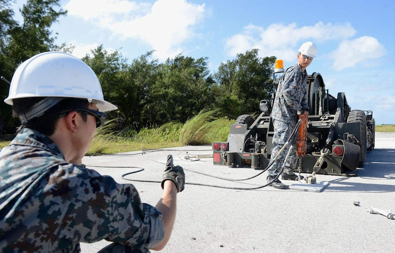 Airmen with the Japan Air Self-Defense Force conduct Mobile Aircraft Arresting System installation training Dec. 6, 2016, at Northwest Field, Guam. A MAAS is a rapid installation emergency system used to recover fighter aircraft returning to and launching from a battle damaged airfield. (U.S. Air Force photo by Senior Airman Arielle K. Vasquez/Released)