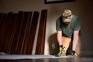 COLORADO SPRINGS, Colo. - Senior Airman Guillermo Loaiza-Martinez, 21st Civil Engineer Squadron structures shop at Peterson Air Force Base, Colo., installs flooring in a fellow Airman's home in Colorado Springs, Nov. 5, 2016. Volunteers from around base helped their wingman so he could focus on his family and healing, rather than the logistics of repairing the flooring. (U.S. Air Force photo by Senior Airman Rose Gudex)