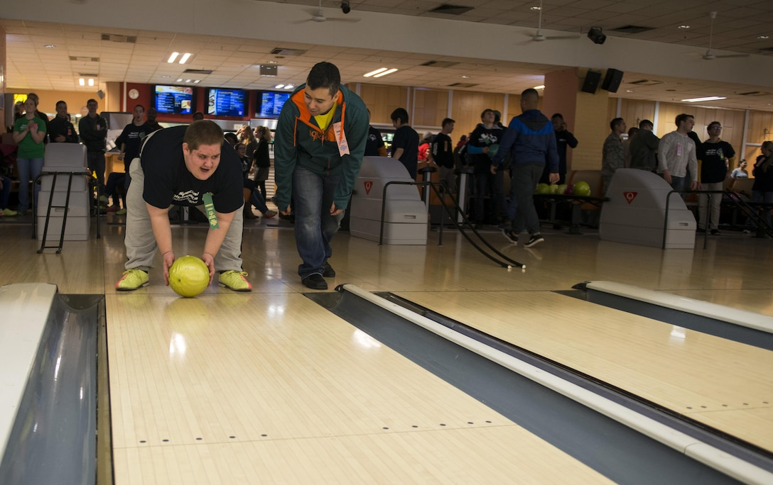 """Tech. Sgt. Antonio Couto, 450th Intelligence Squadron all-source analyst, acts as a """"bowling buddy"""" for Phillip, a Winter Special Olympics participant, at Vogelweh Military Complex, Germany, Dec. 2, 2016. Approximately 70 Airmen from the 450th IS volunteered at several locations throughout the Kaiserslautern Military Community during their second annual service day. (U.S. Air Force photo by Senior Airman Tryphena Mayhugh)"""