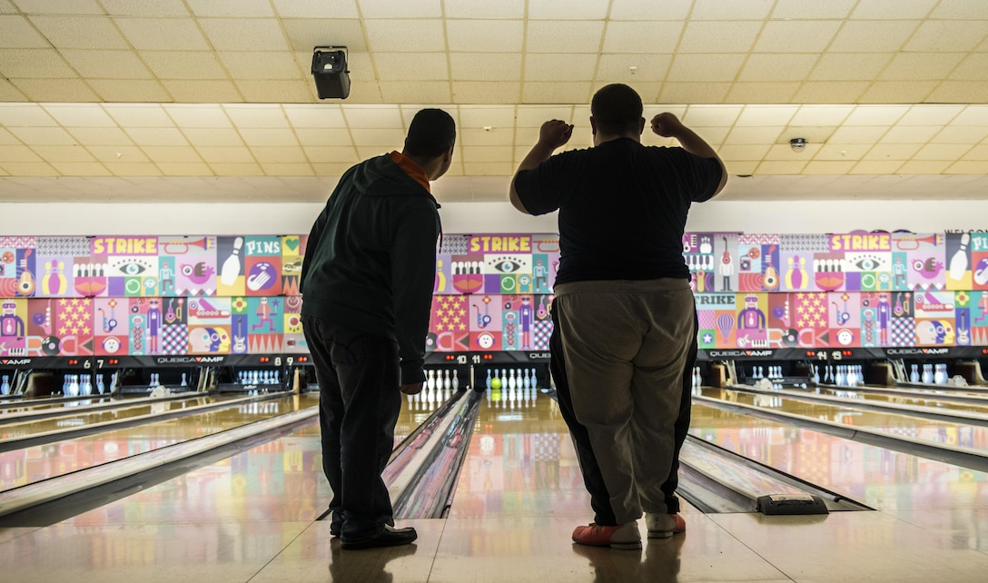 """Tech. Sgt. Antonio Couto, 450th Intelligence Squadron all-source analyst, and Phillip, a Winter Special Olympics participant, watch a bowling ball roll down a lane at Vogelweh Military Complex, Germany, Dec. 2, 2016. Couto volunteered as a """"bowling buddy"""" for the Special Olympics as a part of his squadron's second annual service day. On the first Friday of December, the 450th IS Airmen volunteered throughout the Kaiserslautern Military Community as their way to give back to the community.  (U.S. Air Force photo by Senior Airman Tryphena Mayhugh)"""