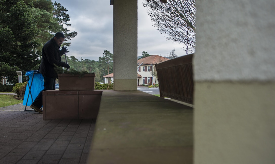Capt. Ryan Tamez, 450th Intelligence Squadron weapons and tactics flight commander, sweeps a pavilion to prepare for the Fisher House's tree-lighting ceremony at Landstuhl Regional Medical Center, Germany, Dec. 2, 2016. Several Airmen assigned to 450th IS helped distribute cookies, set up and tear down the event as a part of the squadron's second annual service day. On the first Friday of December, the 450th IS Airmen volunteered throughout the Kaiserslautern Military Community as their way to give back to the community. (U.S. Air Force photo by Senior Airman Tryphena Mayhugh)