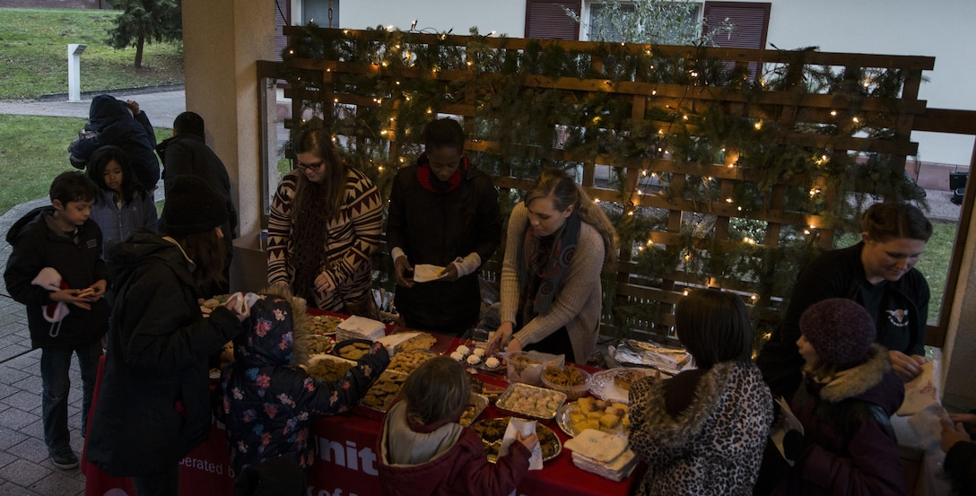 Several Airmen assigned to the 450th Intelligence Squadron pass out cookies at the Fisher House's tree-lighting ceremony at Landstuhl Regional Medical Center, Germany, Dec. 2, 2016. On the first Friday of December, the 450th IS volunteered throughout the community for their annual service day. (U.S. Air Force photo by Senior Airman Tryphena Mayhugh)