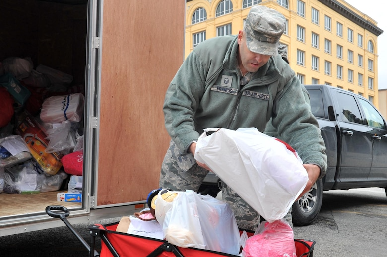 U.S. Air Force Master Sgt. Christopher Francis, 17th Contracting Squadron superintendent, loads toys into a wagon during delivery to the Court Appointed Special Advocates for Children center in San Angelo, Texas, Dec. 8, 2016. The toys are for children in emergency foster care. (U.S. Air Force photo by Staff Sgt. Laura R. McFarlane/Released)