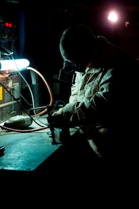 U.S. Marine Lance Cpl. James Sonzogni, a welder with Heavy Equipment Platoon, 1st Maintenance Battalion, 1st Marine Logistics Group, grinds a piece of metal to prepare it for welding during exercise Steel Knight at Marine Corps Air Ground Combat Center Twentynine Palms, Calif., Dec. 8, 2016. Steel Knight 2017 is a 1st Marine Division-led exercise that exposes Marines and Sailors to skill sets necessary to operate as a fully capable Marine air ground task force. Sonzogni is from North Clifton, N.J. (U.S. Marine Corps photo by Sgt. Abbey Perria)