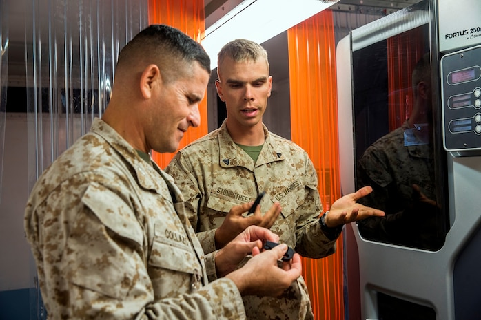 U.S. Marine Cpl. Samuel Stonestreet, a ground radio repairman with 1st Maintenance Battalion, 1st Marine Logistics Group, tells Col. Jaime Collazo, the commanding officer of Combat Logistics Regiment 15, 1st MLG, about an item 1st Maintenance Bn. made with the Expeditionary Manufacturing Facility during the Steel Knight 2017 exercise at Marine Air Ground Combat Center Twentynine Palms, Calif., Dec. 8, 2016. Steel Knight 2017 is a 1st Marine Division-led exercise that exposes Marines and Sailors to skill sets necessary to operate as a fully capable Marine air ground task force. (U.S. Marine Corps photo by Lance Cpl. Adam Dublinske)