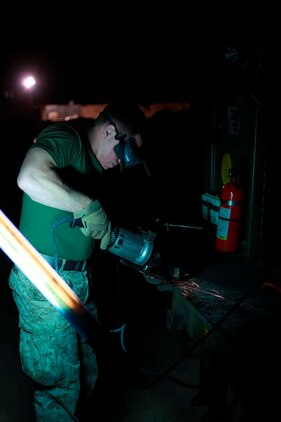U.S. Marine Lance Cpl. James Sonzogni, a welder with Heavy Equipment Platoon, 1st Maintenance Battalion, 1st Marine Logistics Group, grinds a piece of metal to prepare it for welding during exercise Steel Knight at Marine Corps Air Ground Combat Center Twentynine Palms, Calif., Dec. 8, 2016. Steel Knight 2017 is a 1st Marine Division-led exercise that exposes Marines and Sailors to skill sets necessary to operate as a fully capable Marine air ground task force. Sonzogni is from North Clifton, N.J. (U.S. Marine Corps photo by PFC Timothy Shoemaker)