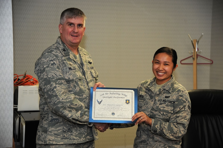 Airman 1st Class Annalou Cumpio, 22nd Comptroller Squadron customer service technician, poses with Col. Albert Miller, 22nd Air Refueling Wing commander, Dec. 1, 2016, at McConnell Air Force Base, Kan. Cumpio received the spotlight performer for the week of Oct. 31- Nov. 4. (U.S. Air Force photo/Airman 1st Class Jenna K. Caldwell)