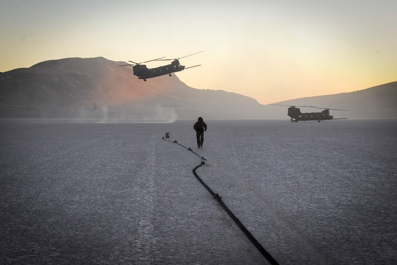U.S. Army flying crew chief assigned to the 160th Special Operations Aviation Regiment sets up the forward area refueling point with two MH-47 aircraft at the Delmar desert landing strip, Nev., Dec. 2. The forward area refueling site was enabled by special tactics Airmen providing security at the landing zone and was conducted within a highly contested environment with an AC-130U providing close air support. (U.S. Air Force photo by Major Richie Harr)