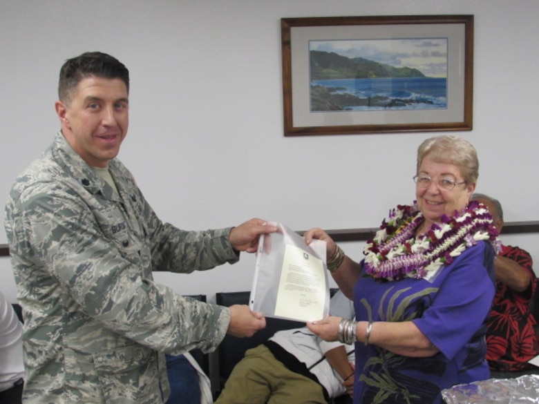 """Lt. Col. Jason Burch, 50th Network Operations Group deputy commander, presents Charlene """"Aunty Char"""" Kaawaloa a congratulatory letter written by Col. DeAnna Burt, 50th Space Wing commander, at Kaena Point Satellite Tracking Station, Hawaii, Wednesday, Dec. 7, 2016. Kaawaloa, a contractor at Kaena Point, was acknowledged in the letter for her 50 years of exceptional service. (Courtesy photo)"""