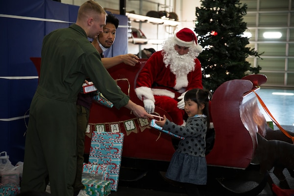 U.S. Marine Corps Lance Cpl. Jeffery Deal, aircraft rescue and firefighting (ARFF) specialist, passes a candy cane to May Yamane, a child with the local orphanage, during the ARFF Tsuta Orphanage Christmas party at Marine Corps Air Station Iwakuni, Dec. 10, 2016.  ARFF holds the celebration annually to help spread holiday cheer to the orphans and to bring service members, their families and Japanese together. Marines volunteered their time and provided the children with a homemade, American meal. After dinner, a special guest came to greet the children. Santa Claus sat in a red sleigh passing out presents and candy canes to the kids. Marines were given the name, age and gender of a child from the orphanage, so they knew what kind of gift to buy for them.