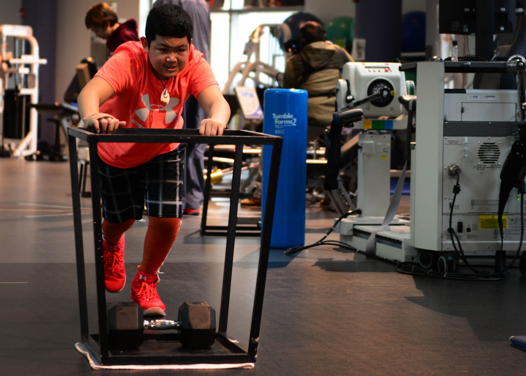 Kimo Martinez pushes a weighted sled during a rehabilitation session at the Center for Intrepid on Joint Base San Antonio-Fort Sam Houston, Texas, Dec. 7, 2016. During the Brussels Airport bombing March 22, 2016, that tragically killed his mother, Kimo and his family sustained multiple injuries that have led to extensive rehabilitative procedures. (U.S. Air Force photo by Senior Airman Chip Pons)