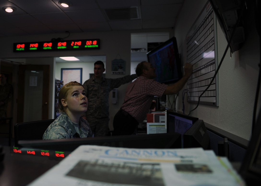 Airman 1st Class Jessie Cox, 27th Special Operations Support Squadron weather forecaster apprentice, monitors systems at base operations, Nov. 21, 2016 at Cannon Air Force Base, N.M. Cannon's unique environmental position requires forecasters to specialize in area-specific details in order to make accurate predictions. (U.S. Air Force photo by Staff Sgt. Whitney Amstutz/released)