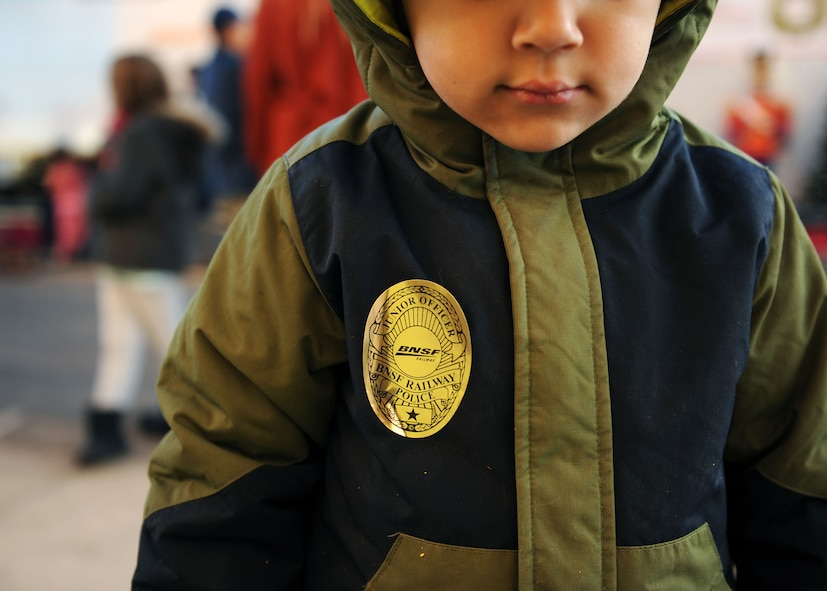 A dependent from Cannon Air Force Base, N.M., waits to board the Holiday Express wearing a novelty BNSF Railway Junior Officer badge, Dec. 1, 2016, at a railyard in downtown Clovis, N.M. For nine consecutive years, the BNSF Railway has invited service members and their loved ones aboard the Holiday Express to enjoy milk, cookies, and a visit from Santa Claus to show their appreciation. (U.S. Air Force photo by Staff Sgt. Whitney Amstutz/Released)
