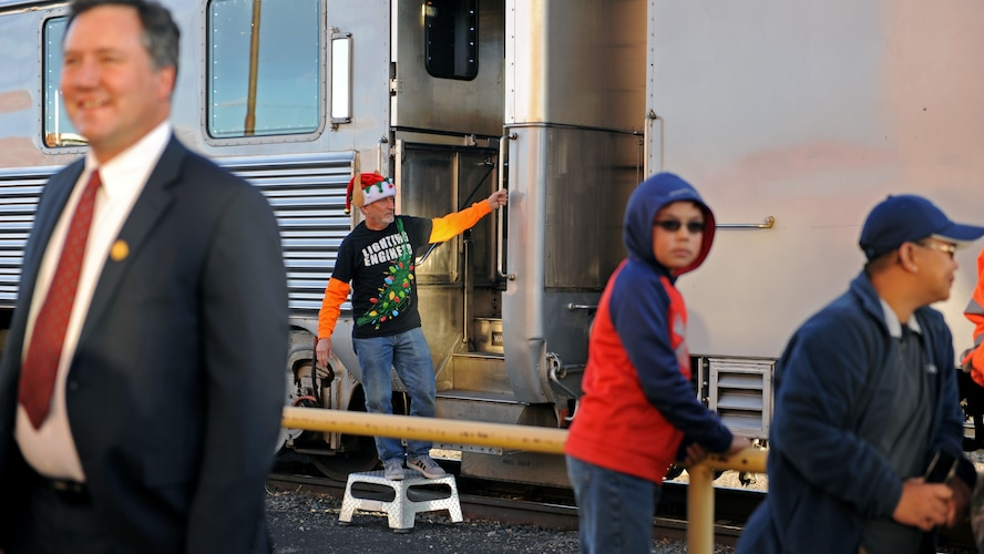 Dressed as an elf, a BNSF Railway employee waits to welcome passengers aboard the Holiday Express, Dec. 1, 2016, at a railyard in downtown Clovis, N.M. For nine consecutive years, the BNSF Railway has invited service members and their loved ones aboard the Holiday Express to enjoy milk, cookies, and a visit from Santa Claus to show their appreciation. (U.S. Air Force photo by Staff Sgt. Whitney Amstutz/Released)