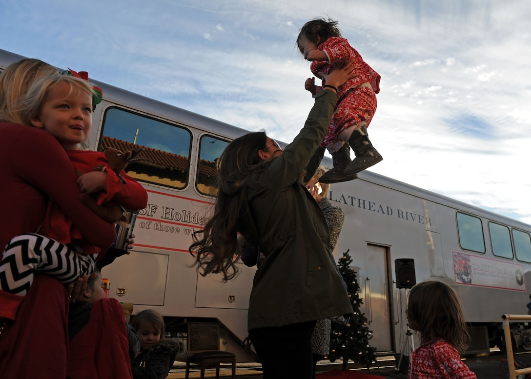 A mother and daughter from Cannon Air Force Base, N.M., play together while waiting to board the Holiday Express, Dec. 1, 2016, at a railyard in downtown Clovis, N.M. For nine consecutive years, the BNSF Railway has invited service members and their loved ones aboard the Holiday Express to enjoy milk, cookies, and a visit from Santa Claus to show their appreciation. (U.S. Air Force photo by Staff Sgt. Whitney Amstutz/Released)