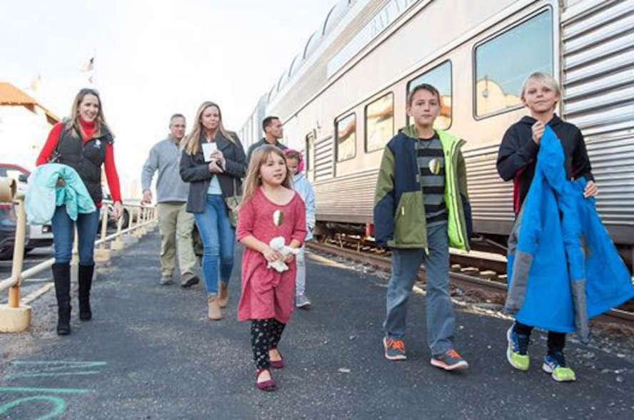 Air Commandos and family members from Cannon Air Force Base, N.M., prepare to board the Holiday Express, Dec. 1, 2016, at a railyard in downtown Clovis, N.M. For nine consecutive years, the BNSF Railway has invited service members and their loved ones aboard the Holiday Express to enjoy milk, cookies, and a visit from Santa Claus to show their appreciation. (U.S. Air Force Courtesy Photo)