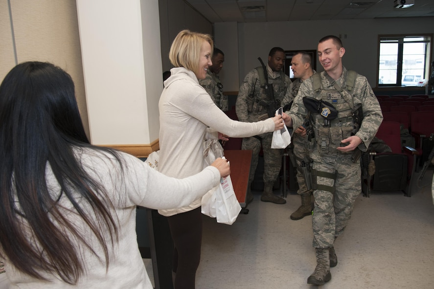 Shaneta Sandoval and Heidi Ringer from the Team Osan Spouse's Club hand out bags of cookies to 51st Security Forces Squadron members during Operation Sweet Treat 2016 on Osan Air Base, Republic of Korea, Dec. 13, 2016. Team Osan Spouses Club sponsored the program that delivered bags of holiday cheer to Osan, Kunsan, Yongsan and Suwon Airmen and Soldiers.  (U.S. Air Force photo by Staff Sgt. Jonathan Steffen)