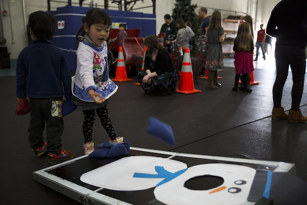 Cocona, a child from ARFF Tsuta Orphanage, plays corn hole during the ARFF Tsuta Christmas party at Marine Corps Air Station Iwakuni, Japan, Dec. 10, 2016. ARFF holds the event annually to help spread Christmas cheer to the orphans and to bring service members, their families and the Japanese together. Activities such as a bouncy house, Christmas cookie decorating and games were available to the children during the event. (U.S. Marine Corps photo by Lance Cpl. Gabriela Garcia-Herrera)