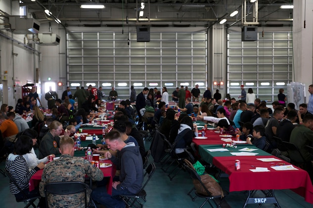 U.S. Marines with Aircraft Rescue and Firefighting, and their families sit together with Japanese locals from ARFF Tsuta Orphanage for a Christmas dinner at Marine Corps Air Station Iwakuni, Japan, Dec. 10, 2016. ARRF holds a Christmas party every year to help spread Christmas cheer to the orphans, and to bring service members, their families and the Japanese together. Marines volunteered their time and provided the children with a homemade, American meal.  (U.S. Marine Corps photo by Lance Cpl. Gabriela Garcia-Herrera)