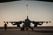 A crew chief with the 407th Expeditionary Aircraft Maintenance Squadron walks past an F-16 Fighting Falcon assigned to the 134th Expeditionary Fighter Squadron at the 407th Air Expeditionary Group, Southwest Asia, Dec. 10, 2016. About 300 Airmen from the 158th Fighter Wing of the Vermont Air National Guard comprise the units. (U.S. Air Force photo by Master Sgt. Benjamin Wilson)(Released)