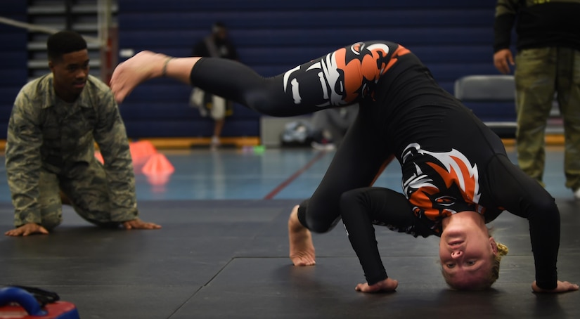 Valentina Shevchenko, UFC Bantamweight fighter, demonstrates a warm up stretch to U.S. Air Force Airmen before training at Joint Base Langley-Eustis, Va., Dec. 8, 2016. Shevchenko trained with the Airmen during a morale visit in preparation for an upcoming fight. (U.S. Air Force photo by Staff Sgt. Natasha Stannard)